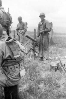 A .30 caliber machine gun on its tripod in the field.