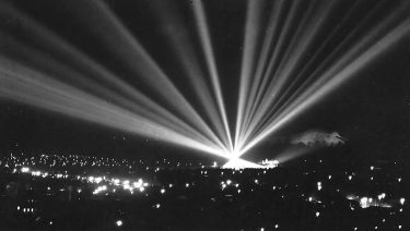 Searchlights over a town - most likely after the war, when blackout restrictions were lifted.