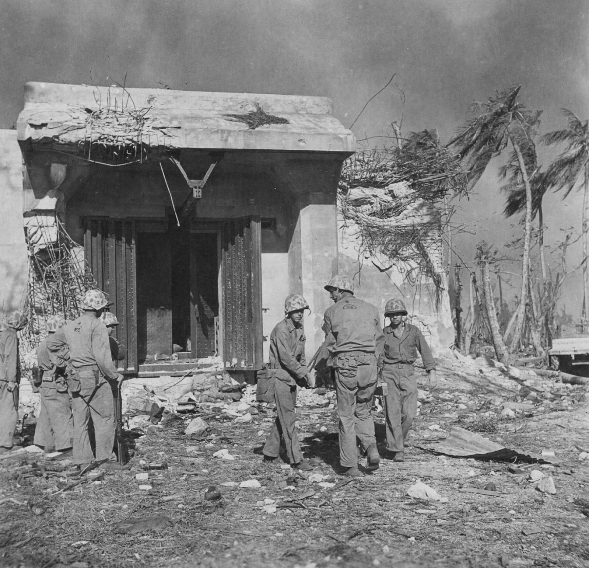 The blockhouse is cleared. Marines discuss their next move. Note the nose of an aerial bomb visible in the open door.
