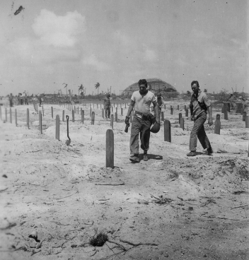 Marines walk through the cemetery, perhaps in search of a buddy's grave.