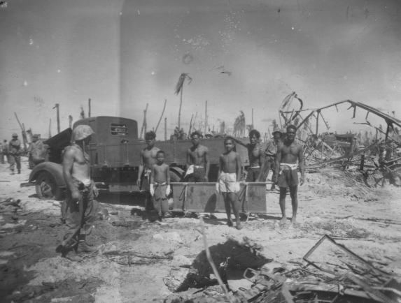 """Rescue Squad on Namur Island: Beside a captured Japanese truck, with a Marine Sgt. in charge, island natives pause in their work of cleaning up area devastated by one of history's heaviest naval barrages."""