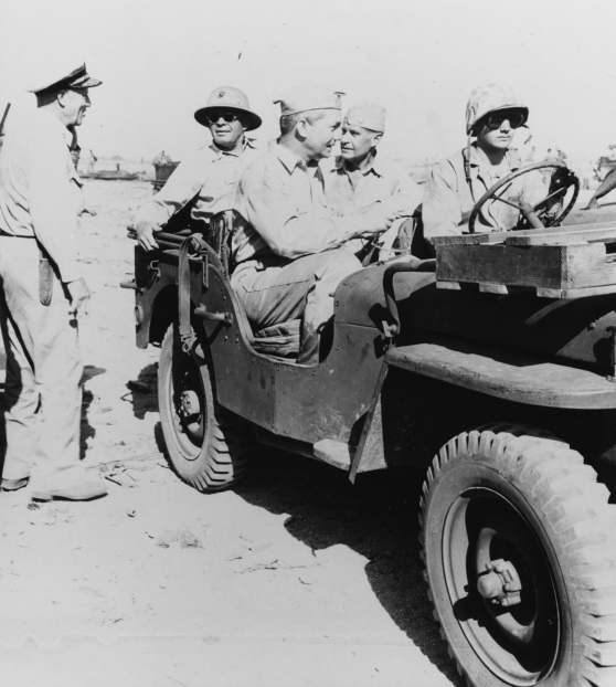 """Secretary of the Navy James Forrestal in front seat, and ADM R.A. Spruance (ComFifthFleet) on back seat with fatigue cap (others unidentified) ride in Jeep around Roi-Namur Islands...."" Naval History & Heritage Command photo."