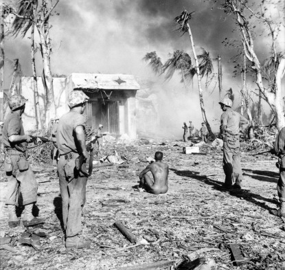 Marines carefully guard a prisoner from the blockhouse.