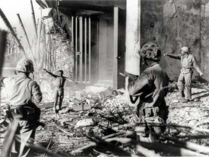 A Japanese soldier (or Korean laborer) staggers out of the blockhouse, while another pokes his head from the rubble.