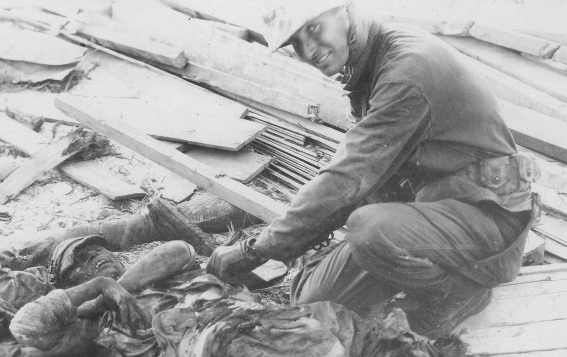 A Marine, possibly a member of a body disposal team (note gloves), checks a Japanese soldier's pockets. Official USMC photo.