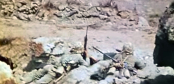 Two Marines waiting for the signal to advance. Still from USMC combat camera.