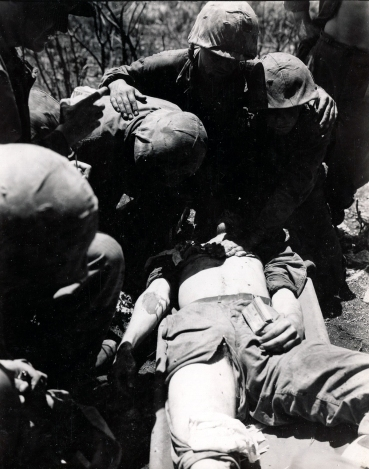"""Navy medical corpsmen aid a wounded Marine who escaped a Jap ambush laid in the mountainous jungle for mop-up units attempting to take native civilians to safety. June 1944, Saipan, Gillespie."" (NARA Photo)"