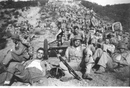 "Rest break on a march through the Camp Pendleton boondocks. NCO in front is Celio ""Chic"" Sperandio. Note covered M1917 machine gun on wheeled cart."