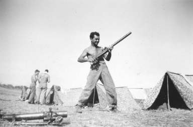A Charlie Company machine gunner demonstrates a somewhat unorthodox firing stance. Pendleton tent camp. 1943.