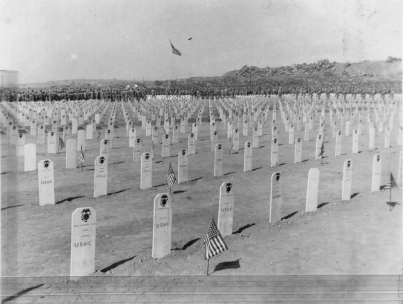 Cemetery at Iwo Jima. All hands are saluting the flag. Note wrecked aircaft piled in background.