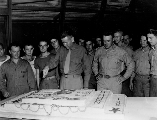 Colonel Walter I. Jordan cuts the cake for the Marine Corps Birthday, 10 November 1944. Looking on is Major Paul Treitel, commanding 1/24.