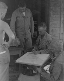 Colonel Hart writes out an order for Brunelli. Saipan.