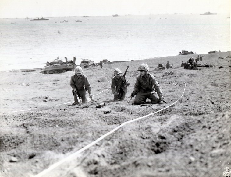 Engineers probe the soft sand for mines on 19 February 1945. These are 5th Division Marines; note two are wearing protective flash paint. USMC photo.