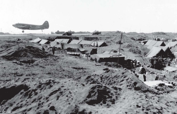 A C-47 loaded with wounded men takes off from Airfield #1. Tents in the foreground are a field hospital. USMC photo.