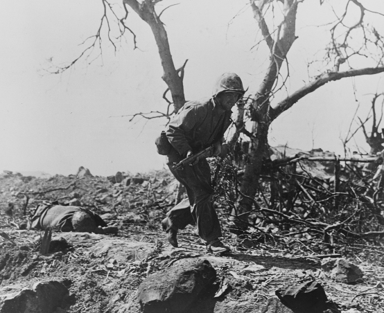 A Marine under fire runs past a dead Japanese soldier...